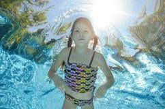 Barnet simmar i den undervattens- pölen, flicka har gyckel i vatten arkivfoto