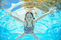 Barnet simmar i den undervattens- pölen, flicka har gyckel i vatten royaltyfri fotografi