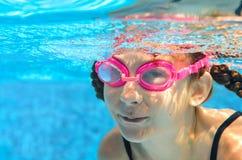 Barnet simmar i den undervattens- pölen, den lyckliga aktiva flickan i skyddsglasögon har gyckel i vatten, ungesport på familjsem Fotografering för Bildbyråer