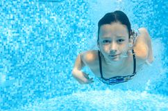 Barnet simmar i den undervattens- simbassängen, den lyckliga aktiva flickan dyker och har gyckel under vatten, ungekondition och  fotografering för bildbyråer