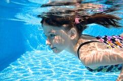 Barnet simmar i den undervattens- simbassängen, den lyckliga aktiva flickan dyker och har gyckel under vatten, ungekondition och  arkivbild