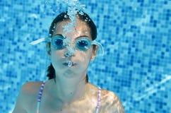 Barnet simmar i undervattens- lycklig aktiv tonåring för simbassäng som flickan dyker, och har gyckel under vatten, ungekondition Arkivbilder