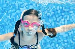 Barnet simmar i undervattens- lyckliga aktiva flickadykar för simbassäng och har gyckel under vatten, ungesport på familjsemester royaltyfria bilder