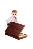 Barnet sitter med en resväska som är full av guldtackor Arkivbild