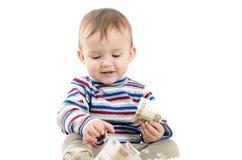 Barnet sitter med hantlar i hand Arkivfoto