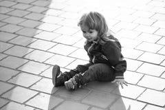 Barnet sitter på asfalten Pysen sitter på trottoar royaltyfri fotografi