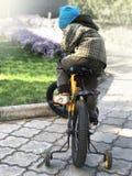 Barnet sitter på en cykel i parkera i nedgången arkivfoto