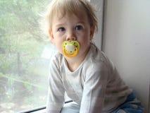 Barnet sitter på fönstret Royaltyfria Bilder