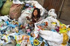 barnet sitter under hans föräldrar arbetar på förrådsplats, i Katmandu, Nepal Arkivfoto