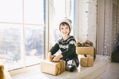 Barnet sitter vid fönstret på en solig juldag och gör ut med gåvor i askar som slås in i papper iklätt stuckit varmt royaltyfria foton