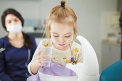 Barnet sköljer ut munnen och spottar i special vask arkivbild