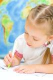 Barnet skriver genom att använda en penna royaltyfria foton