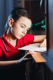 Barnet skriver i en anteckningsbok Royaltyfri Fotografi