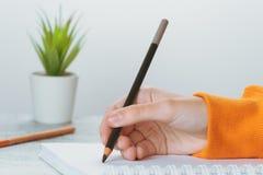 Barnet skriver med blyerts i en anteckningsbok arkivfoto