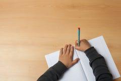 Barnet skriver på en anteckningsbok Royaltyfri Bild