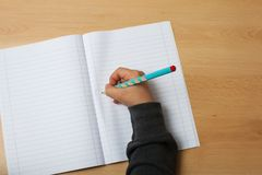 Barnet skriver på en anteckningsbok Royaltyfri Foto