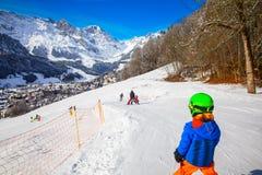 Barnet som är klart för att skida som är berömt, skidar semesterorten i schweiziska fjällängar arkivbilder