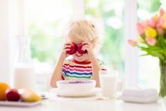 Barnet som äter frukostungen med, mjölkar och sädesslag royaltyfria foton