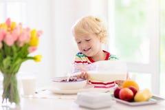 Barnet som äter frukostungen med, mjölkar och sädesslag royaltyfria bilder