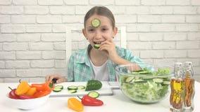 Barnet som äter grön sallad, ungen i kök, flicka äter den nya grönsaken, sund mat royaltyfri fotografi
