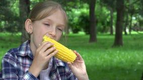 Barnet som äter utomhus- kokt havre parkerar in, den hungriga flickan äter sund mellanmålmat 4K stock video