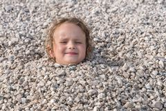 Barnet som begravas under stenarna, endast huvud, kan ses arkivbild