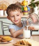 barnet som den lyckliga tillbringaren mjölkar, häller Arkivfoton