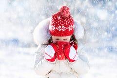 Barnet som dricker varm choklad i vinter, parkerar Ungar i snö på Chr Royaltyfria Bilder