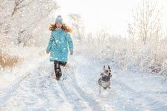 Barnet som går på vintern, parkerar royaltyfri bild