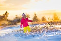 Barnet som har gyckel i snöig vinter, parkerar Royaltyfri Foto