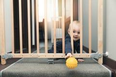 barnet som kastar bollen bort till och med säkerhet, utfärda utegångsförbud för framme av trappa royaltyfri foto