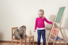 Barnet som leker med katten, skolar. Arkivbilder