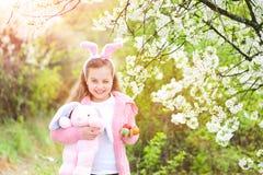 Barnet som ler med kaninen, gå i ax i trädgård med att blomstra träd fotografering för bildbyråer
