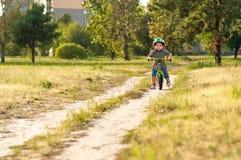 Barnet som rider en cykel Royaltyfria Bilder