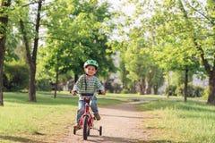 Barnet som rider en cykel Arkivfoton