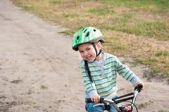 Barnet som rider en cykel Arkivbild