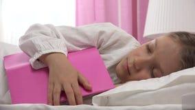 Barnet som sover efter läsebok, unge faller sovande i hennes säng, flicka hemma stock video