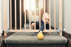 Barnet som spelar bak säkerhet, utfärda utegångsförbud för framme av trappa royaltyfri foto
