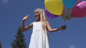 Barnet som spelar ballonger parkerar in, flickaståenden som går den utomhus- lyckliga ungeframsidan royaltyfria bilder
