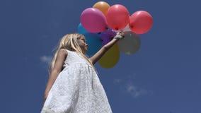 Barnet som spelar ballonger parkerar in, flickaståenden som går den utomhus- lyckliga ungeframsidan royaltyfri foto
