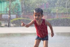 Barnet som spelar i regnet som faller i vattnet, parkerar arkivbild