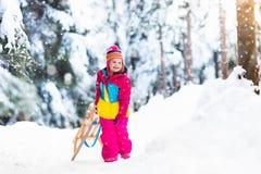 Barnet som spelar i snö på släde i vinter, parkerar arkivbild
