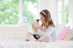 Barnet som spelar med, behandla som ett barn katten Unge och kattunge royaltyfri foto