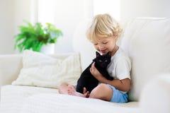 Barnet som spelar med, behandla som ett barn katten Unge och kattunge royaltyfria foton