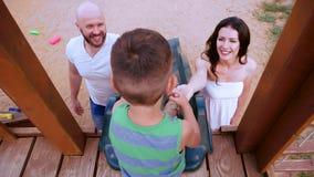 Barnet som spelar med föräldrar, pojkeritten till barn`en s, glider, en moder, och fadern stöttar hans son, lycklig familj stock video