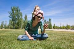 Barnet som spelar med moderläsningtelefonen parkerar in Arkivfoton