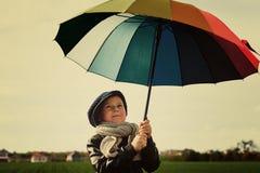 Barnet som står under ett kulört paraply på den gröna ängen Royaltyfri Fotografi
