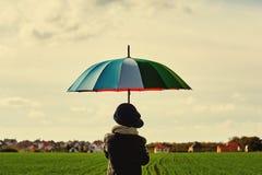 Barnet som står under ett kulört paraply på den gröna ängen Arkivbild