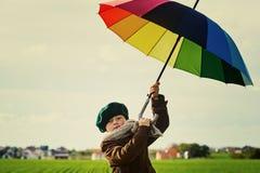 Barnet som står under ett kulört paraply på den gröna ängen Arkivbilder
