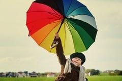 Barnet som står under ett kulört paraply på den gröna ängen Royaltyfri Bild